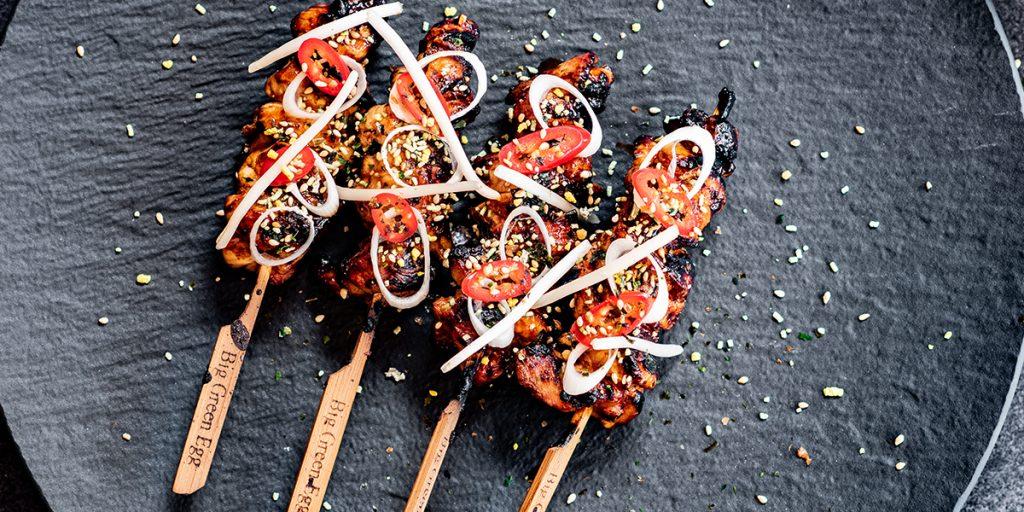 Fertige Hähnchenspieße auf schwarzem Teller mit Sesam bestreut.