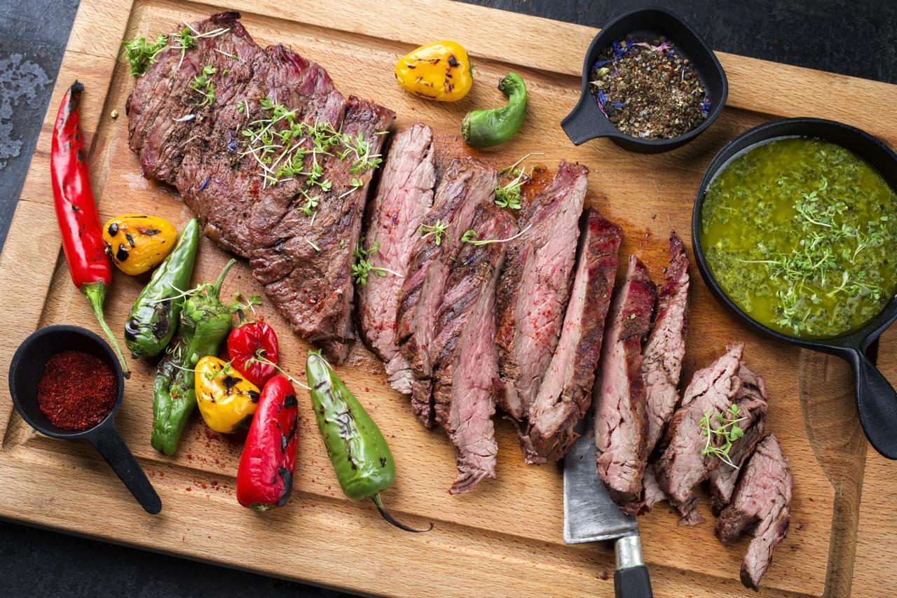 Flat Iron Steak auf Holzbrett mit Chilischoten und Chimichurri