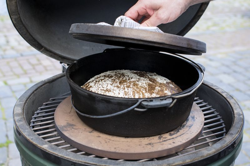 Gebackenes Brot im Dutch Oven. Der Deckel wird angehoben.